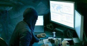 Hooded haker in front of computer